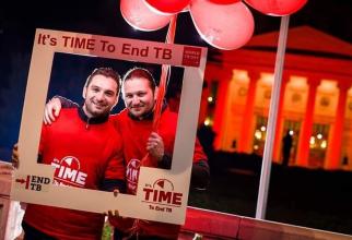 Ștefan Răduț (stânga), liderul Asociației pentru Sprijinirea Pacienților cu Tuberculoză Multidrog Rezistentă și vicepreședinte în TB Europe Coalition, în fața Ateneului Român luminat în roșu
