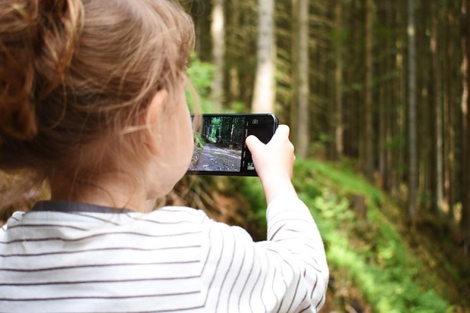 Copil ținând un smartphone în mână  FOTo: Pixabay