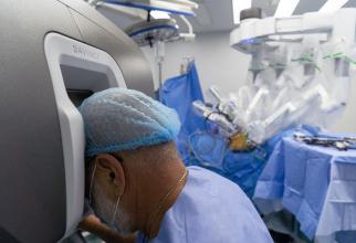 Chirurgul Bogdan Marțian în timp ce operează cu ajutorul sistemului robotic daVinci. Foto: Sanador
