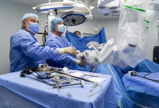 Poziționarea brațelor operatorii ale robotului chirurgical. Dr. Bogdan Marțian (stânga) și Dr. Eugen Mihăilă. Foto: SANADOR
