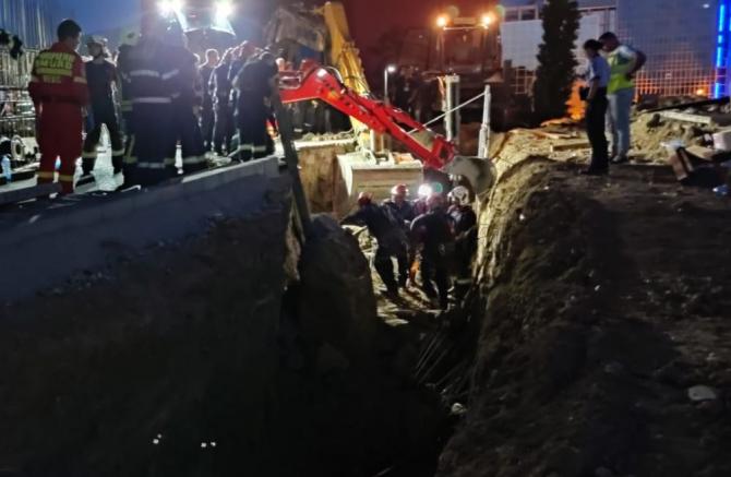 Abia la 21.30 au reușit pompierii să scoată ultimul muncitor care fusese acoperit de malul de pământ surpat. Foto: ISUBIF
